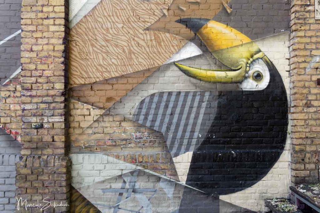 Urban Art am RAW-Gelände - Mural von einem exotischen Vogel am Backsteingebäude