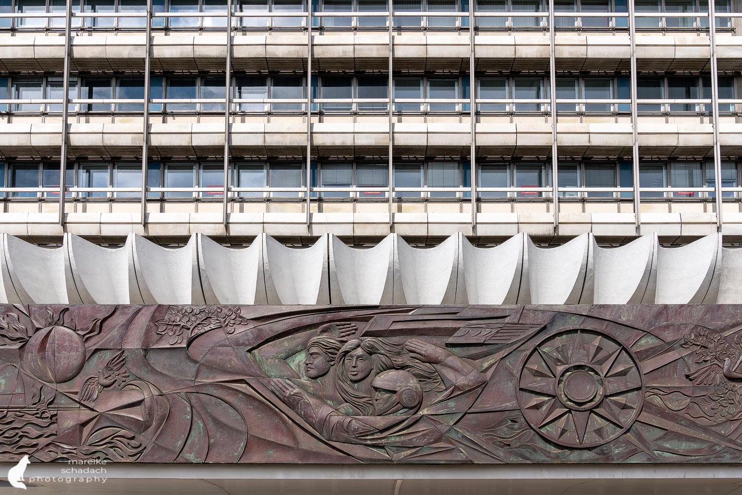 """DDR Architektur in Berlin: Kupferrelief """"Der Mensch überwindet Zeit und Raum"""" am Haus des Reisens."""
